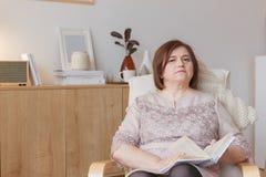 Милая старшая женщина сидя назад на кресле с интересной книгой стоковое изображение