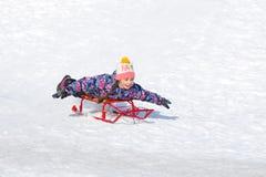 Милая счастливая девушка на скелетоне сползая вниз с холма на снеге стоковые изображения