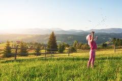 Милая счастливая маленькая игра ребёнка outdoors в раннем утре в лужайке и восхищать Mountain View Скопируйте космос для стоковое фото