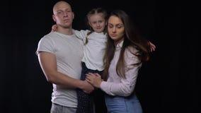 Милая съемка славных полных семьи, матери и отца держа их дочь видеоматериал