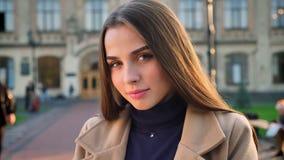 Милая уверенная кавказская женщина стоит все еще и смотрит сторону камеры прямую, жизнерадостную усмехаясь и спокойный взгляд видеоматериал