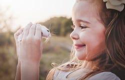 Милая усмехаясь девушка держа белого хомяка - ретро взгляда Стоковые Изображения RF