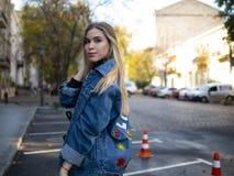 Милая усмехаясь девушка с роскошными волосами в куртке джинсовой ткани стоит в парковке для автомобилей на открытом воздухе стоковые изображения