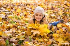 Милая усмехаясь маленькая девочка лежа на упаденных листьях и держа букет желтых кленовых листов в ее руках стоковое изображение