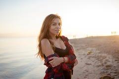 Милая усмехаясь маленькая девочка, портрет на предпосылке захода солнца моря Стоковая Фотография