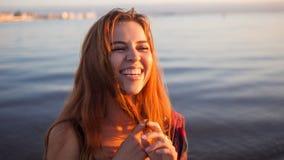 Милая усмехаясь маленькая девочка, портрет на предпосылке захода солнца моря Стоковое Фото