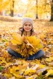 Милая усмехаясь маленькая девочка сидя на упаденных листьях в парке осени и держа букет желтого leav клена стоковые изображения rf