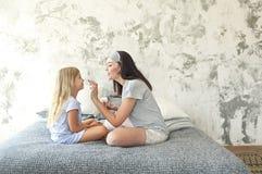 Милая усмехаясь мать и дочь прикладывая сливк стороны стоковые изображения