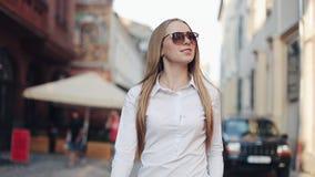 Милая усмехаясь молодая женщина в стильном взгляде уверенно идет вниз с улицы, нося солнечные очки Утеха жизни, активная акции видеоматериалы