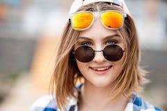 Милая усмехаясь рубашка белокурой девушки нося checkered и 2 солнечного очк смотрят с шаловливыми глазами стоковые фотографии rf