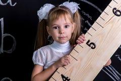 Милая школьница стоя перед доской как предпосылка держа огромного правителя раскосно Увеличенный взгляд стоковые изображения rf