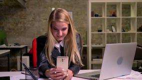 Милая энергичная кавказская женщина имеет видео- звонок по ее телефону, говорит счастливо и смотрит холодок веб-камеры иллюстрация штока