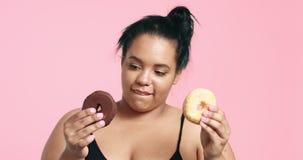 Милая curvy черная девушка есть donuts акции видеоматериалы