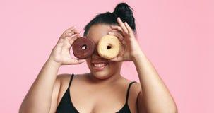 Милая curvy черная девушка есть donuts видеоматериал