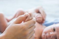 Милая newborn мать владением младенца большим пальцем руки Стоковые Фото