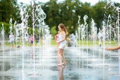 Милая preteen девушка играя в фонтанах на заново восстановленном квадрате Lukiskes в Вильнюсе, Литве Ребенок имея потеху с водой  стоковое фото