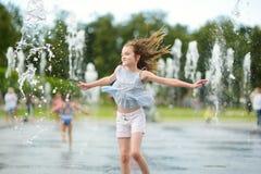 Милая preteen девушка играя в фонтанах на заново восстановленном квадрате Lukiskes в Вильнюсе, Литве Ребенок имея потеху с водой  стоковое изображение