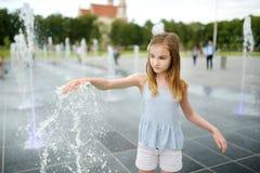 Милая preteen девушка играя в фонтанах на заново восстановленном квадрате Lukiskes в Вильнюсе, Литве Ребенок имея потеху с водой  стоковое изображение rf
