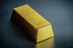 Миллиард слитка бара золота на голубой предпосылке Размещено раскосно стоковое изображение