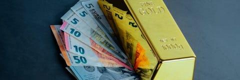 Миллиард слитка бара золота на фоне счетов доллара и евро стоковые изображения