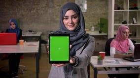 Милое арабское женское положение и показывать зеленый экран на ее планшете пока стоящ холодок со славной улыбкой, коллегами дальш сток-видео