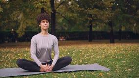 Милое брюнет протягивает ноги в представлении ` s сапожника сидя на циновке йоги после этого гнуть вперед ослаблять назад и закры видеоматериал