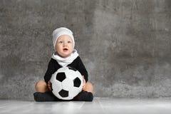 Милое изображение младенца держа футбольный мяч стоковые фото