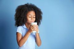 Милое курчавое Афро-американское питьевое молоко девушки Стоковые Изображения