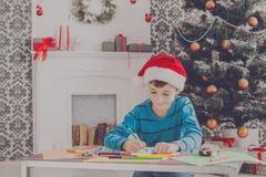 Милое письмо к santa, ожидание сочинительства мальчика для рождества Стоковые Фотографии RF