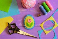 Милое handmade пасхальное яйцо войлока, покрашенный комплект потока, ножницы, кольцо, валик штыря, утиль войлока и листы на фиоле Стоковые Фотографии RF