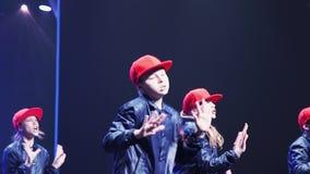 Милые девочка-подростки и мальчики в темных костюмах с красным крышек танцем synchronically сток-видео
