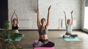 Милые девушки делают тренировки йоги под наведением опытного инструктора Они начинают с asanas извива, тогда кладут сток-видео