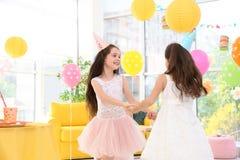 Милые девушки играя совместно на вечеринке по случаю дня рождения Стоковая Фотография