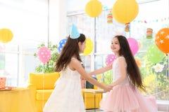 Милые девушки играя совместно на вечеринке по случаю дня рождения Стоковое Изображение