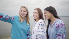 Милые девушки нося длинное платье моды лета делая selfies на предпосылке озера или реки Кавказец 2 видеоматериал