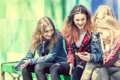 Милые девушки сидя на стенде в парке и смеяться над Стоковые Изображения RF