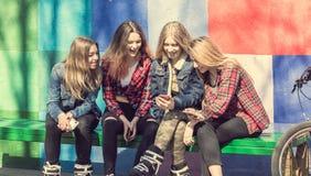 Милые девушки сидя на стенде в парке и смеяться над Стоковая Фотография RF