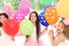 Милые девушки с воздушными шарами на вечеринке по случаю дня рождения внутри помещения Стоковая Фотография RF