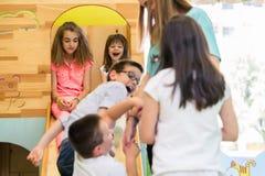Милые девушки усмехаясь во время, который наблюдали playtime в современном детском саде стоковые изображения rf
