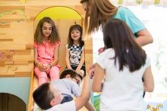 Милые девушки усмехаясь во время playtime, который наблюдал молодой учитель стоковые фотографии rf