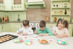 Милые дети украшают печенья на таблице в домашней кухне Стоковая Фотография