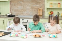 Милые дети украшают печенья на таблице в домашней кухне Стоковые Изображения RF