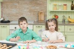 Милые дети украшают печенья на таблице в домашней кухне Стоковые Изображения