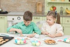 Милые дети украшают печенья на таблице в домашней кухне Стоковое Изображение RF