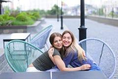 Милые женщины сидя на кафе снаружи Стоковое Изображение