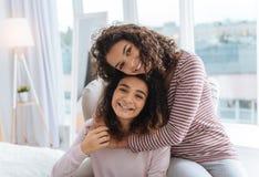 Милые курчавые с волосами сестры обнимая плотно и усмехаясь Стоковая Фотография