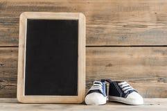 Милые маленькие ботинки младенца на деревянной предпосылке Стоковая Фотография RF