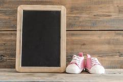 Милые маленькие ботинки младенца на деревянной предпосылке Стоковое Фото