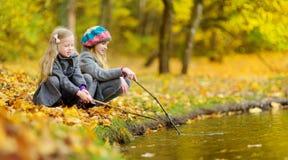 Милые маленькие девочки играя водой на красивый день осени Счастливые дети имея потеху в парке осени стоковое изображение rf