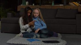 Милые маленькие девочки печатая сообщение на умном телефоне акции видеоматериалы